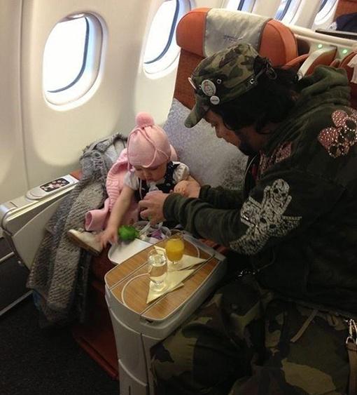 Фил и малышка сидят в самолете и, судя по всему, завтракают. В своем