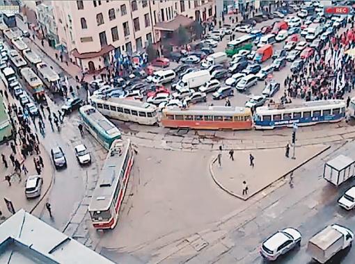 Колонна людей движется к мэрии. Дорогу им преграждает колонна из трамваев. Фото: videoprobki.ua.