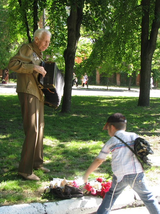 Пока идут торжества, Владимир Самуилович развлекает прохожих, играя на стареньком баяне. Фото: Евгения РУДНИЦКАЯ