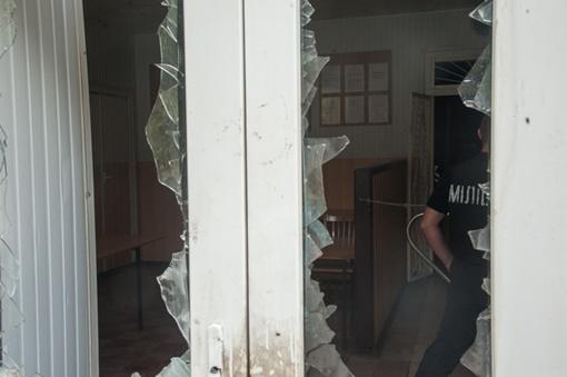 В райотдел никого не пускают, за разбитыми стеклами входных дверей видны сотрудники милиции. Автор фото - Максим Войтенко