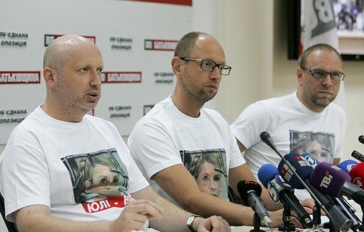 Турчинов, Яценюк и Власенко хранят свои футболки с лицомм экс-премьера для пресс-конференций. Фото: УНИАН.