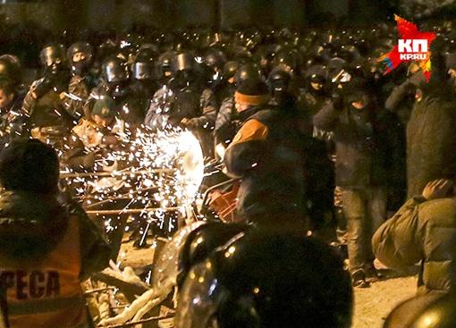 Люди в штатском распиливают железные конструкции баррикад. Фото: БЕРОЕВА Нигина