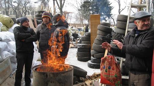 Субботним утром людей возле здания немного, несколько человек греются возле бочек с костром. Фото: Анна Мищишина