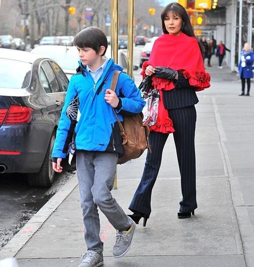 Кэтрин, одетая в строгий брючный костюм и красное пончо, следовала за мужем и детьми. Фото: Splash News