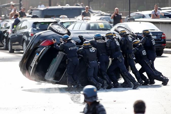 На дорогах перевернутые протестующими автомобили. Фото: REUTERS