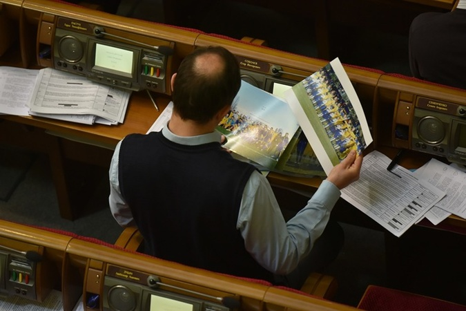 Соболев рассматривает фото с прошедшего футбольного матча между депутатами и журналистами.