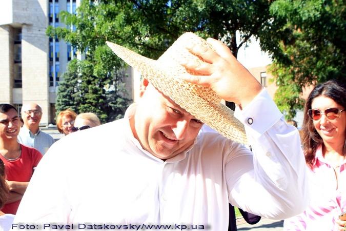 Мэр примерил соломенную шляпу на фоне городского совета.
