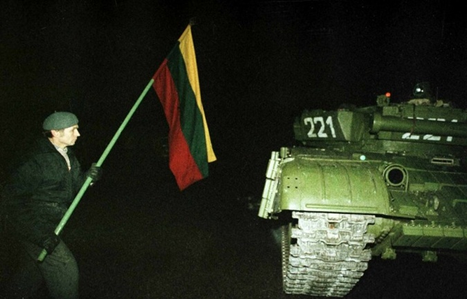 Один из протестующих с флагом около советского танка.