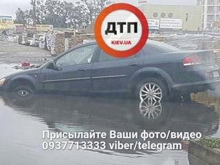 В Киеве автомобиль утонул в луже, выезжая с парковки супермаркета