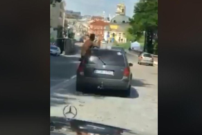 acffd1361399 По центу столицы разъезжал автомобиль, из окна которого высунулся почти  голый мужчина со спиртным в руках. Об этом сообщило издание